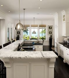 Dark floors, white cabinets, and carerra marble
