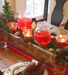 Easy but festive centerpiece idea -- rustic box, filled with red candles, greenery and pinecones, on a cheery runner.