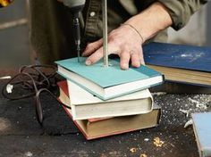 """Thread books on center rod and use 2"""" screws to secure each book to the one below it."""