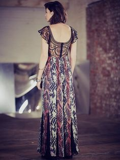 Wild Hearts Maxi   Water color like chiffon maxi with abstract print and scalloped lace insets on hem. Jet beadwork and sequin detail over embroidered mesh back and flutter sleeves. Ornate embroidered appliqué across bodice. Zip closure on back.