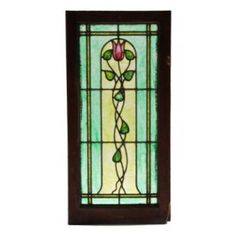 very elegant c. 1910-15 craftsman or arts & crafts style leaded art glass window. fabricated by the ornamental glass studios of chicago-based h. eberhardt. the brightly colored art glass window contains a simple grid pattern with a centrally located flower with flowing vines and leafage. the american arts & crafts stained glass window consists primarily of semitransparent textured and cathedral roll glass. the wood sash frame is original and largely intact. measures 37 x 17 3/4 inches.