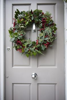 Embellish the front door with a holly wreath studded with scarlet berries.