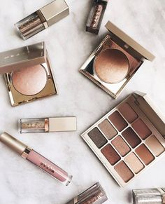 pinterest: @lilyosm   beautiful makeup flatlay golden makeup stila brand highlighters liquid lipsticks eyeshadow palettes