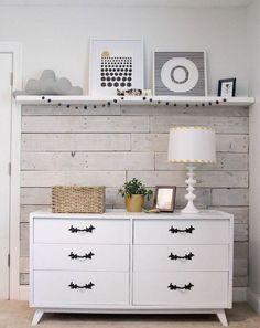 lambris bois blanc, commode blanche à poignées en fer forgé et une étagère blanche dans la chambre de bébé
