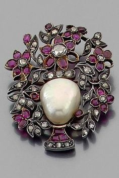 An 18th century ruby, diamond, gold and silver brooch. Designed as a basket of flowers, set with rubies and diamonds, centring a half-pearl, mounted in gold and silver. #Antique #brooch #Georgian