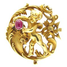 Ruby Gold Rococo Cherub Love Brooch. A beautifully modelled French 18ct gold brooch which is all about Love! The cherub is holding a cabochon cut ruby. It would make a special present for a loved one. c 1910