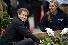 Prince Harry plants vegetables in a raised bed with members of the Student Volunteer Army during a visit to the University of Canterbury in Christchurch