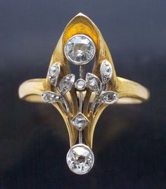 ART NOUVEAU  Floral Ring   Gold Diamond  H: 2.3 cm (0.91 in)   Marks: '18' with French poincon  French, c.1900  Ring Case  8 rose cut diamonds 0.10 cts approx  Old cut diamonds one 0.20 cts approx, the other 0.15 cts approx