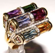 green tourmaline, rhodolite garnet, citrine, amethyst, iolite and blue topaz, separated by rows of diamonds set in solid 18K white gold. On the sides of the shank are columns of more gemstones in a rounded Fleur