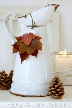 Fall decor - so simple: vintage tinware pitcher with leaf accent and pinecones at base!