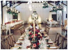 Fall wedding reception with floral chandeliers and long white tables set with wooden X-back chairs, natural wooden chargers, brilliant autumn centerpiece florals and tall taper candles. Event design by Easton Events, florals by Beehive Events. Image by Eric Kelley at Pippin Hill Farm & Vineyards near Charlottesville, VA.