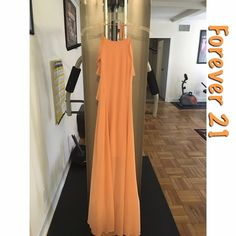 """Flounced halter maxi dress Forever 21 flounced halter maxi dress. Size: Large. Fits fitted over a flowy overlay. Includes a half slip that comes above knee. Color: Salmon. Appears peach in photo, but is more light coral in photo. 100% Polyester. Measured from chest: 30"""". From bust to hem: 56"""". Note: there are two very slight dark marks due to washing on sides of dress (in photo 3). Forever 21 Dresses Maxi"""