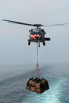 An MH-60S carries supplies at sea. by Official U.S. Navy Imagery