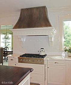 A custom faux finish was created to resemble oxidized zinc on this kitchen range hood, creating a focal point in this lovely kitchen.