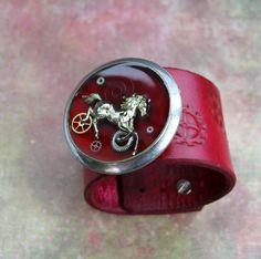 Steampunkový náramek Originální steampunkový červený náramek z hovězí kůže (dobarvovaný kvalitními barvami), doplněný o ražbu a dozdobený steampunkem (kolečko o průměru 4 cm). Zapínání variabilní, lze jednoduše přešroubovat na požadovanou délku, určen na obvod zápěstí 15 -18.5 cm. Šířka náramku: 4,5 cm, tloušťka kůže 3 mm, celková délka 23 cm. Dárkově ...