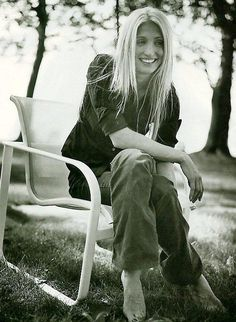 Carolyn Bessette, blond hair, wide leg pants, black shirt. Shot by Bruce Weber