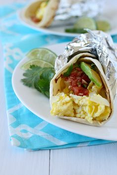 Breakfast Tacos: ½ tbsp. unsalted butter ¼ cup chopped onion 3-4 large eggs Splash of milk Salt and pepper 2 8-inch tortillas 6 tbsp. crumbled Mexican cheese such as cotija ¼ cup chopped cilantro Salsa, for serving Sliced avocado, for serving