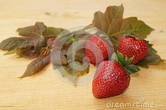 Strawberries and leaves on wooden background