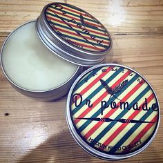 pomade container with barber pole inspired logo