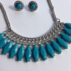 New Statement Necklace New, never worn statement necklace with matching earrings.  Statement necklace has bluish been and crystal stones, the chain is silver in color and is adjustable, the earrings have the same color stone and are surrounded in crystals. Unlisted Jewelry Necklaces