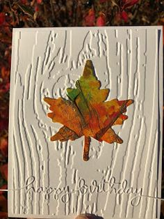 handmade birthday card for the CAS Watercolour October Challenge  ... embossing folder woodgrain background in white ... negative space maple leaf in bright Fall colors in the tissue paper with watercolor technique ... beautiful!