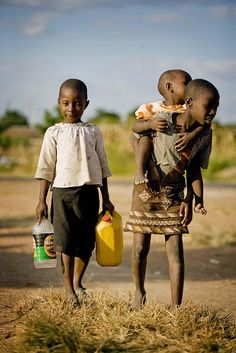 ZIMBABWE CHILDREN carrying their water containers as they walk towards one of 22 boreholes that the AusAid have helped to fund in partnership with Unicef in the Budiriro District. The area was badly affected by a cholera outbreak.Africa