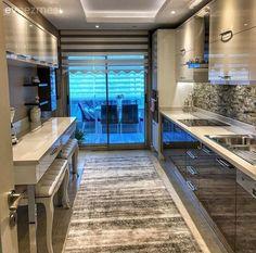 Sadece tek tarafında dolapları olan modern stil mutfağının karşı bölümüne, üst dolaplar, ekstra alan sağlayan raf ve   altına pufları yerleştirdiği bir tezgah ekleyerek; hem bolca depolama alanı, hem...