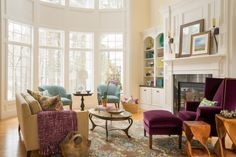 Windows that stretch to the ceiling make this transitional living room feel grand yet inviting. A plush purple velvet chair with a matching ottoman rests by the fireplace, while a beige sofa sits adjacent to a pair of blue chairs. A built-in bookshelf displays colorful accessories and books for the avid reader.