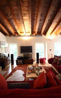 Un grande salotto con soffitto inclinato, #travi in legno a vista e ...