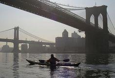 Kayaking under the Brooklyn and Manhattan Bridges, East River, New York City.