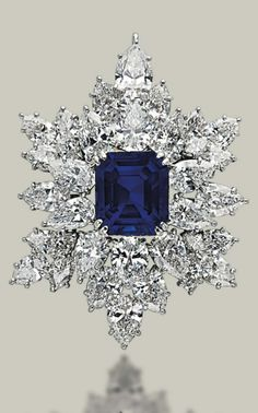 A SAPPHIRE AND DIAMOND BROOCH/PENDANT, BY HARRY WINSTON  The rectangular-cut sapphire, weighing approximately 9.67 carats, within a cluster of pear and marquise-shaped diamonds, mounted in platinum, 4.2 cm With maker's mark of Jacques Timey for Harry Winston