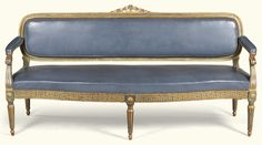 A suite of Italian blue lacquered and carved giltwood seat furniture, Parma, circa 1780 comprising a sofa and four chairs, the sofa with an oblong back with curved ends with ribbon-tied floral top-rail, padded back, downscrolled arms on serpentine seat, the seat-rail with stylised Greek-key motif on fluted tapering legs and toupie feet, with similarly carved chairs with oval backs