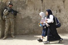 Girls walk past a U.S. soldier on a patrol with the Iraqi police in Baghdad's Ameen district October 14, 2008.