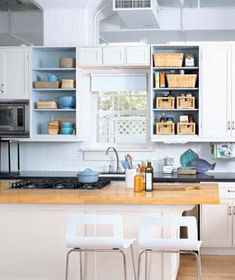 Keep open kitchen shelves uncluttered by stashing items in airy rattan baskets.