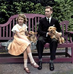 King George VI and then Princess Elizabeth sitting on a bench with their corgi dogs in the grounds of their London home.