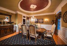 Hier sehen wir die luxuriöse formelle Speisesaal mit seiner komplizierten Bodenbelag, der Teppich und Hartholz mischt. Die reich verzierten Möbel und geschnitztem Holz Credenza pflegen Sie die luxuriöse Atmosphäre.