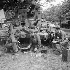 A Cromwell tank crew of 4th County of London Yeomanry, 7th Armoured Division, preparing a meal in front of their vehicle, 17 June 1944. Left to right: Trooper Arthur Nelson, Trooper William Leonard and Sergeant A Gordon.