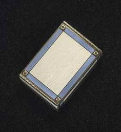 A JEWELED SILVER AND GUILLOCHÉ ENAMEL CIGARETTE CASE BY FABERGÉ, WORKMASTER VLADIMIR SOLOVIEV, ST. PETERSBURG, 1908-1917. Rectangular with rounded corners, enameled overall in translucent white over a wavy guilloché ground, within borders of light blue enamel over a cross hatched ground, the corners applied with silver-gilt rosettes between chased gold laurel borders, with diamond-set thumb-piece.