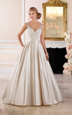This ball gown with sash wedding dress from Stella York is full romance! Dolce satin creates a stunning silhouette from beaded straps and sweetheart neckline to voluminous skirt. Linear beading highlights the neckline while a satin sash at the waist flattering the figure. The back swopes into a low opening from illusion beaded straps and is followed by fabric covered buttons that run the length of the long train. Pockets give this dress a modern update. This satin ball gown is available in…