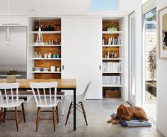 Featuring reclaimed wood from the original house, a single sliding door covers only half of the kitchen pantry. As the door slides, china and glassware are revealed on one side; the other side holds Anne's design library and favored heirlooms. The sliding door follows a track installed in the concrete underfloor; the shelves are supported by recessed steel brackets, strong enough to hold the weight of a man—or a baby. An additional full-size pantry is located inside the laundry room, toward…