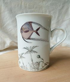Enjoy your cup of tea or coffee in this graceful, unique mug. Part of our original fishy fish dinnerware collection, the 9 oz cup features an angel fish floating above a bulbous sea plant thats barely disguising a friendly fishy fellow. All of our pieces are decorated and kiln-fired at 1400 in our studio for a permanent, heirloom quality finish. They are food safe, dishwasher safe and microwave safe.  See our shop for the entire fishy fish dinnerware line. *QUANTITY DISCOUNT* Mix and Match…