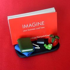 This cute hand-crafted polymer clay business card holder would make the perfect gift for your favorite teacher! A bit of gloss varnish has been