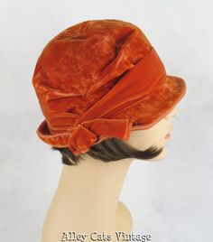 1920s  burnt orange velvet asymmetrical cloche with a wide hat band and side tie.  6 part crown