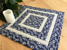 """Quilted square table topper or wall hanging handmade with a blue fabric with white floral design. The accent fabric is white with a tiny blue print. The patchwork top is quilted with a criss-cross pattern in the center then """"stitched in the ditch"""" around the two border areas. The backing and hand stitched double binding are finished with the blue and white floral print fabric. Measures 18"""" square."""