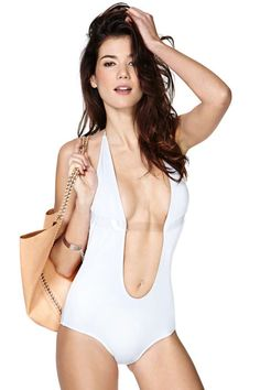 The coolest white swimsuit featuring a plunging front and back with clear strapped detailing and halter neck.