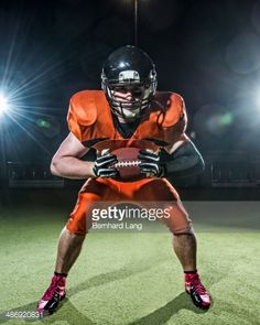 American Football Player holding ball out : Stock-Foto