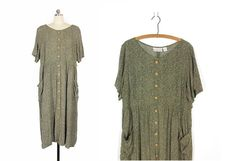 Vintage 90s sage green micro print dress. This dress slips on over the head and has a row of decorative wooden buttons all the way down the front. Features a scoop neck, loose elbow length sleeves, an empire waist and slouchy side hip pockets. Draped tie yoke in back. Baggy fit. Falls to around mid-calf on most women.