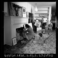 Art collector Diana Zlotnick removes a painting from storage in her fireplace as her husband Harry and daughters watch, 1965.    Diana was an early collector of artists such as Andy Warhol, Robert Raushenberg, Ed Rusha, Wallace Berman, and George Herms.  Her collection has been shown at SFMOMA.