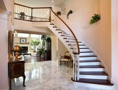 An elegant entryway with a curved staircase above the white marble flooring and a view of the living room. Would you love to have this in your home?