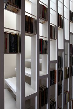 Staircase Bookshelves - Doesn't have to be a pass-through design.  Could be built like a checkerboard with cavities and flush squares alternating in the spaces between the studs.  -- staircase_bookcase_tamir_addadi_01